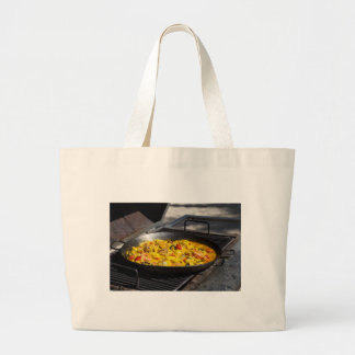 Paella is cooked on a grill large tote bag