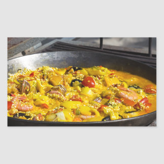 Paella is cooked on a grill rectangular sticker