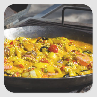 Paella is cooked on a grill square sticker
