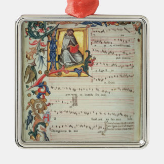 Page of musical notation with a historiated square metal christmas ornament