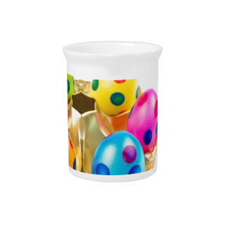 Painted easter eggs in gold tray isolated on white pitcher