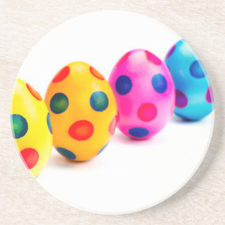 Painted easter eggs in row on white background drink coaster