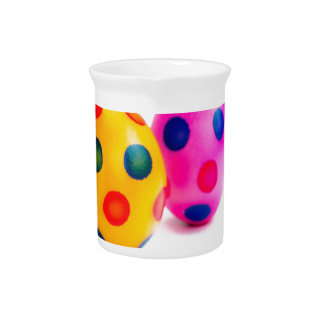 Painted easter eggs in row on white background drink pitchers
