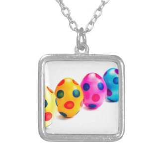 Painted easter eggs in row on white background silver plated necklace