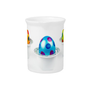Painted easter eggs standing in porcelain egg cups pitcher