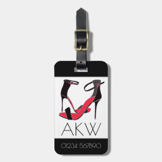 Pair of high heeled shoes on black with monogram luggage tag