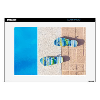"""Pair of slippers at edge of swimming pool skin for 15"""" laptop"""