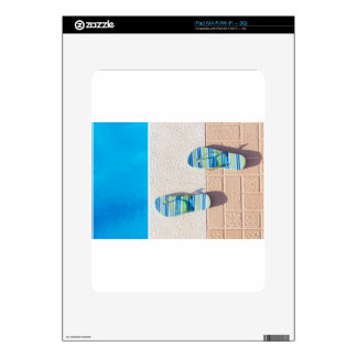 Pair of slippers at edge of swimming pool skin for iPad