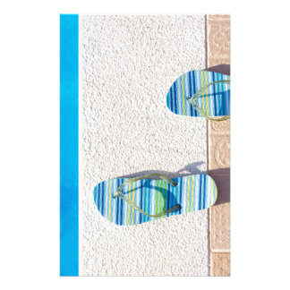 Pair of slippers at edge of swimming pool stationery