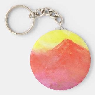 Paisaje abstracto anaranjado del volcán de la llavero redondo tipo pin