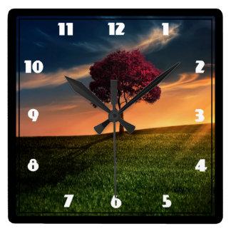 Paisaje asombroso con un árbol rojo en la puesta reloj cuadrado