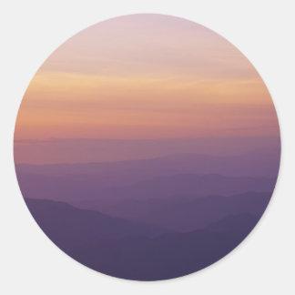 Paisaje montañoso de la puesta del sol pegatina redonda