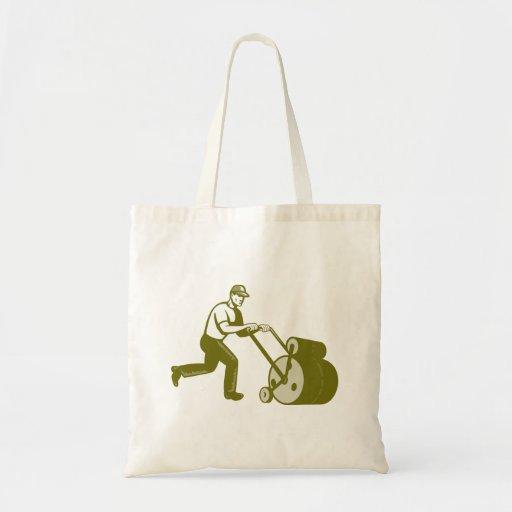 Paisajista del jardinero que empuja el rodillo del bolsa tela barata