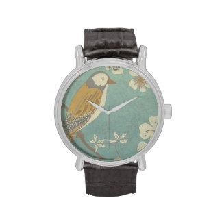Pájaro amarillo, gris y beige encaramado en una relojes