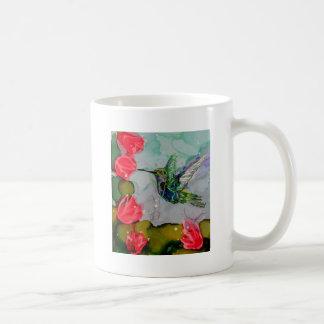 Pájaro del tarareo y flores rojas tazas