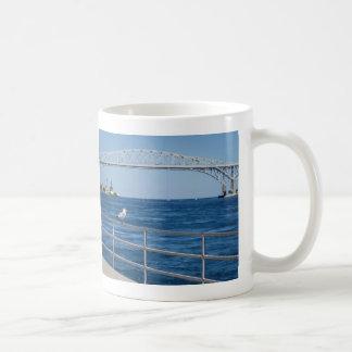 Pájaro en el puente del agua azul taza de café