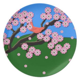 Pájaro en placa rosada de las flores de cerezo platos