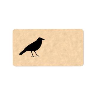 Pájaro negro del cuervo en un modelo del pergamino etiqueta de dirección