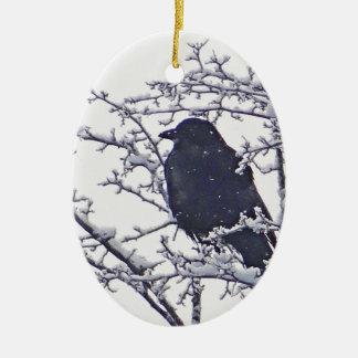 Pájaro negro lindo en ramas nevosas adorno navideño ovalado de cerámica