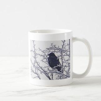 Pájaro negro lindo en ramas nevosas taza clásica