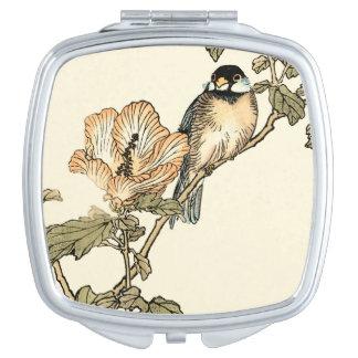 Pájaro oriental encaramado en rama espejo de viaje