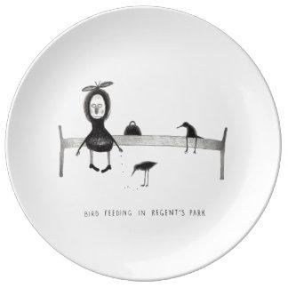 Pájaro que alimenta en el parque del regente platos de cerámica