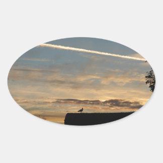 Pájaro silueteado contra el sol poniente pegatina ovalada