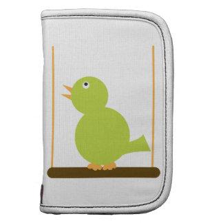 Pájaro verde en un folio del carrito de la perca planificadores