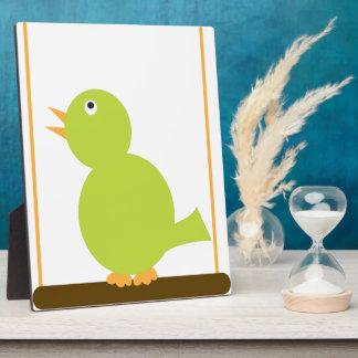 Pájaro verde en una placa de la perca