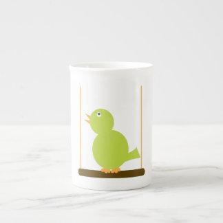 Pájaro verde en una taza de la especialidad de la  taza de porcelana