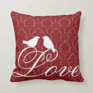 Pájaros del amor en la almohada roja del damasco