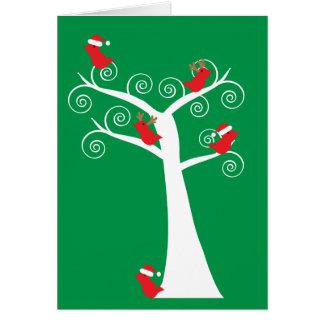 Pájaros del navidad en una tarjeta del árbol