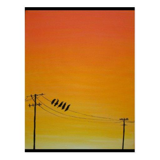 Pájaros en un alambre en la puesta del sol postal