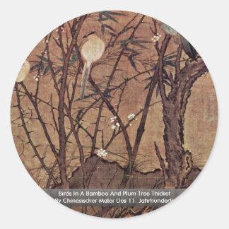 Pájaros en un matorral del árbol del bambú y de pegatina redonda