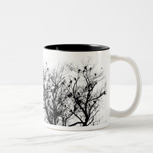 Pájaros negros en árboles tazas