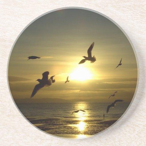 Pájaros que vuelan en la puesta del sol posavaso para bebida