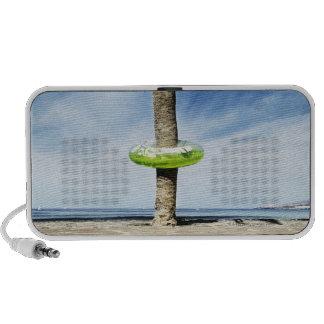 Palmera grande en una playa arenosa con inflable iPod altavoces