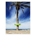 Palmera grande en una playa arenosa con inflable tarjetas postales