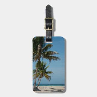 Palmera y playa blanca de la arena etiqueta para equipaje