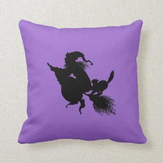 Palo de escoba y gato de la bruja en púrpura cojín