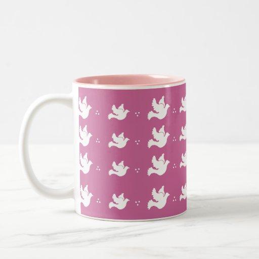 Palomas blancas en la taza rosada del fondo