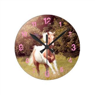 Palomino Paint Pferd galoppiert über eine Wiese Wanduhr
