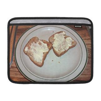 Pan tostado con mantequilla en una placa fundas para macbook air
