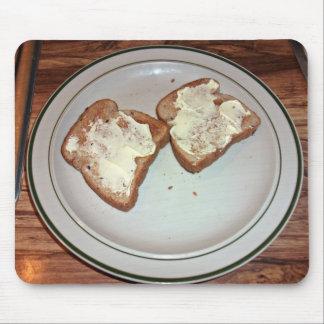 Pan tostado con mantequilla en una placa alfombrilla de ratones