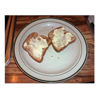 Pan tostado con mantequilla en una placa tarjetas postales