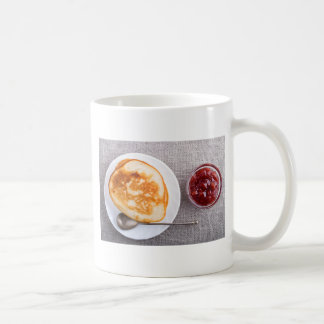Pancakes and a glass cup with strawberry jam