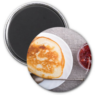 Pancakes and a glass cup with strawberry jam magnet