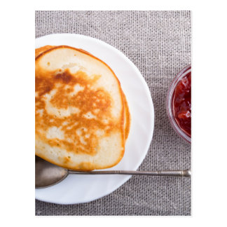 Pancakes and a glass cup with strawberry jam postcard