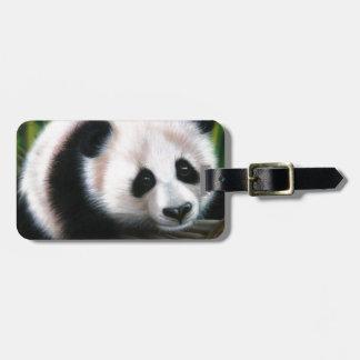Panda del bebé que equilibra en un registro etiquetas maletas