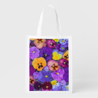 Pansy flowers floating in bird bath with dew grocery bag